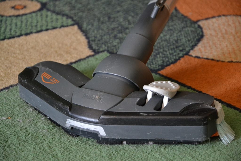 Staubsauger macht bunten Teppich sauber